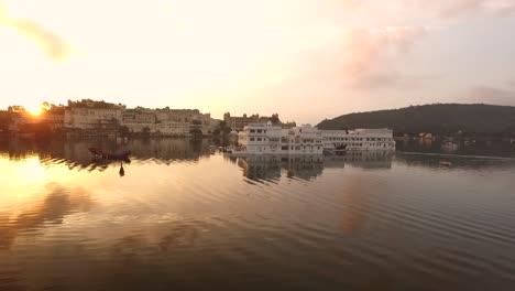 Boats-circle-the-Taj-Lake-Palace-on-Lake-Pichola-in-Udaipur-India-at-sunset
