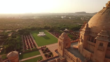 Una-Vista-Aérea-Muestra-Pájaros-Volando-Sobre-El-Palacio-De-Umaid-Bhawan-En-Jodhpur,-India-1