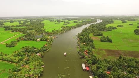An-aerial-view-shows-a-houseboat-sailing-down-a-river-in-Kerala-India