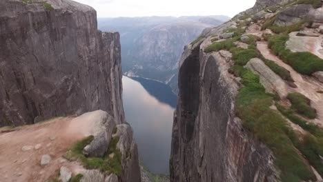 An-aerial-view-shows-a-couple-standing-on-Kjeragbolten-a-boulder-on-the-Kjerag-mountain-in-Rogaland-Norway-1