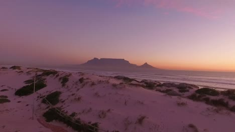 Table-Mountain-is-seen-at-sunset-from-the-coast-of-Bloubergstrand-in-Cape-Town-South-Africa