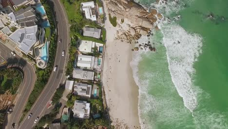 A-bird-seyeview-shows-cars-driving-by-the-beach-of-Camps-Bay-in-Cape-Town-South-Africa