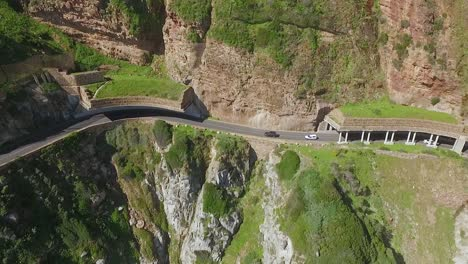 An-aerial-view-shows-cars-are-seen-driving-by-the-seaside-along-Chapman-s-Peak-in-South-Africa