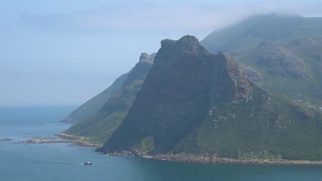 A-ship-sails-along-the-cliffs-and-mountains-on-the-Cape-Of-Good-Hope-region-near-Cape-Town-South-Africa-1