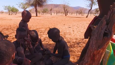 A-young-African-Himba-tribal-boy-leans-against-a-tree-in-a-small-village-in-Namibia