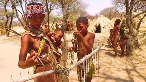 Familia-De-Bosquimanos-Tribales-San-Africanos-En-Sus-Chozas-En-Una-Pequeña-Aldea-Primitiva-En-Namibia-África