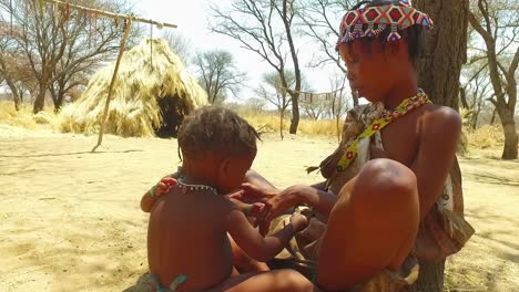 African-San-tribal-woman-and-her-baby-in-a-small-primitive-village-in-Namibia-Africa