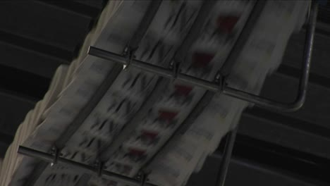 A-fast-zoom-into-newspapers-moving-along-the-top-of-an-assembly-line