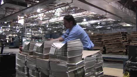 Un-Trabajador-Apila-Periódicos-En-Una-Imprenta