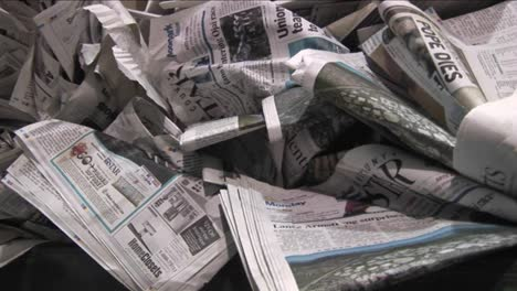 Pan-across-old-crinkled-newspapers-sit-in-a-recycling-bin-in-a-factory