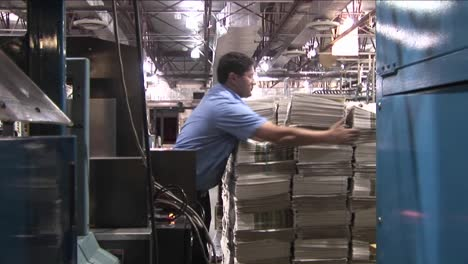 A-machine-stacks-and-binds-newspapers-in-a-factory-then-we-zoom-into-a-stack-of-papers-1