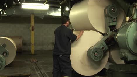 Workers-watch-paper-rollers-in-newspaper-factory-1