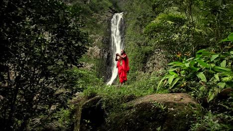 A-Hawaii-native-performs-a-ritual-in-front-of-a-tropical-waterfall