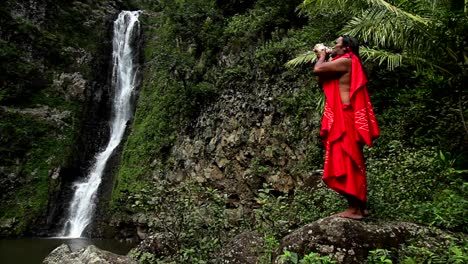 A-Hawaii-native-performs-a-conch-ritual-in-front-of-a-tropical-waterfall