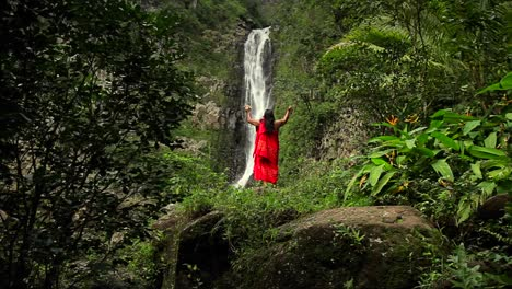 A-Hawaii-native-holds-out-his-hands-to-bless-a-waterfall-1