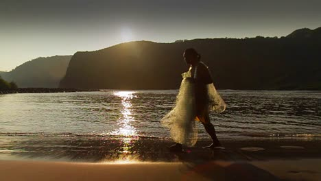 Classic-shot-of-Polynesian-fisherman-walking-on-a-beach-with-his-fishing-net
