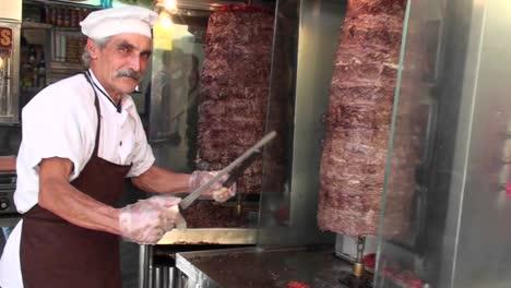 Un-Carnicero-Afila-Su-Cuchillo-Ante-Dos-Trozos-De-Carne-Hilando
