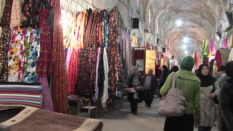 Women-in-chadors-pass-carpets-in-a-bazaar-in-Iran-