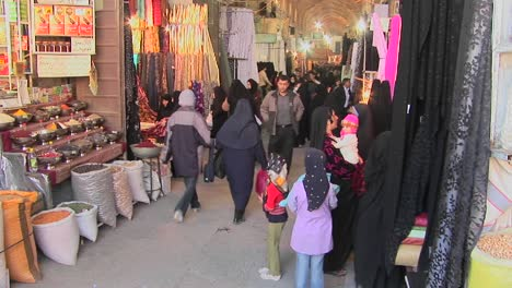 Women-wearing-headscarfs-and-chadors-pass-through-a-bazaar-in-Iran-