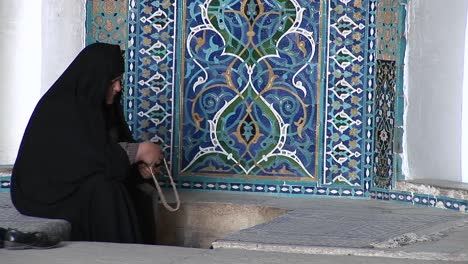 A-woman-wearing-a-chador-sits-before-a-carpet-in-a-bazaar-in-Iran-