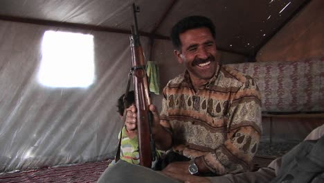 A-man-holds-an-assault-rifle-in-a-tent-in-Iran-