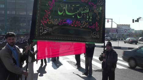 Protesters-hold-a-sign-at-a-busy-intersection-in-Iran-