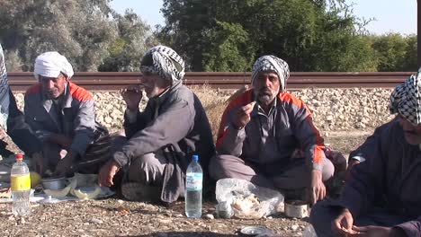 Men-wearing-the-traditional-muslim-headdress-or-keffiyeh-sit-by-a-fire-outside-in-Iran-