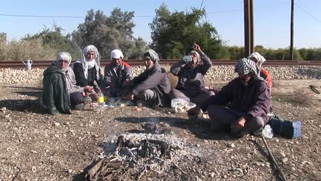 Men-wearing-the-traditional-muslim-headdress-or-keffiyeh-sit-by-a-fire-outside-in-Iran-1