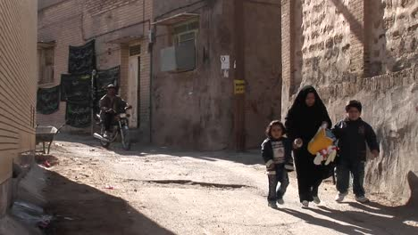 A-woman-wearing-a-chador-walks-with-two-children-down-an-ancient-alley-in-Iran