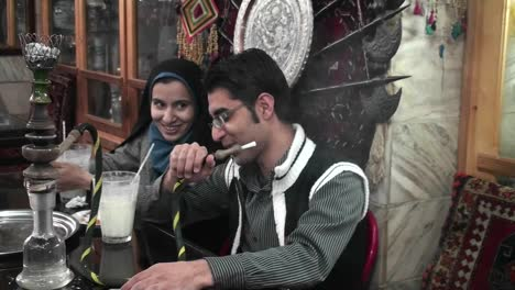 A-woman-wearing-a-headscarf-and-a-man-smoke-a-hookah-pipe-in-an-outdoor-cafe-in-Iran-