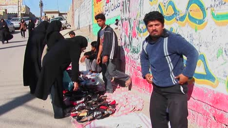 A-women-wearing-chadors-buy-from-vendors-near-a-wall-covered-in-graffiti-in-an-urban-area