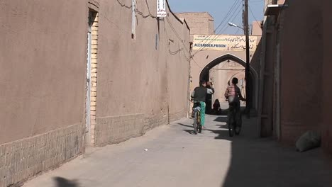Two-children-ride-bicycles-down-an-ancient-alley-way-in-Iran-