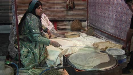 A-woman-wearing-a-headscarf-bakes-lavash-bread-on-a-tandori-oven