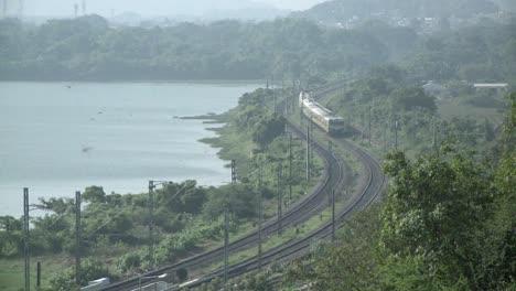 Un-Tren-Que-Se-Aproxima-Viaja-Por-Una-Ruta-Rural-Cerca-De-Un-Lago-
