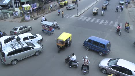 Vehicles-and-pedestrians-travel-through-a-busy-intersection