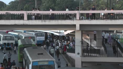 People-gather-in-a-bus-station-getting-on-and-off-buses-and-crossing-an-overhead-walkway