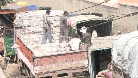 Workers-transfer-stacks-of-papers-from-one-truck-to-another