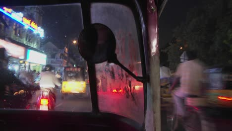 A-blurred-view-from-a-motorized-rickshaw-driving-down-a-street-at-night