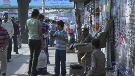 A-young-boy-wants-to-buy-something-from-a-street-vendor-and-his-mother-buys-it-for-him