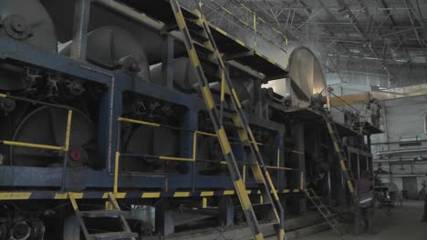 A-man-carries-a-large-pile-of-paper-over-his-head-through-a-manufacturing-plant