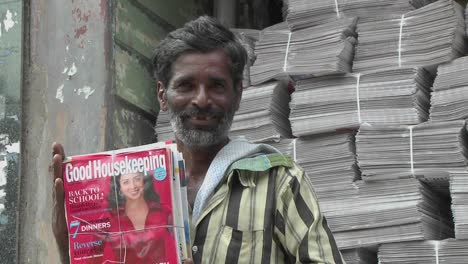 A-man-is-smiling-while-holding-a-bundle-of-magazines