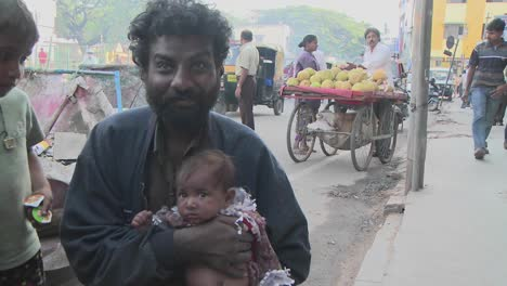 People-on-an-Indian-street-watch-something-above-their-heads-then-a-man-holding-a-baby-smiles-gets-up-and-leaves