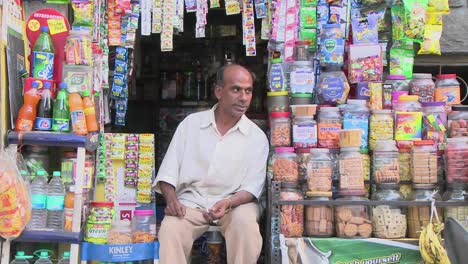 People-walking-in-front-of-man-sitting-in-front-of-his-street-stall