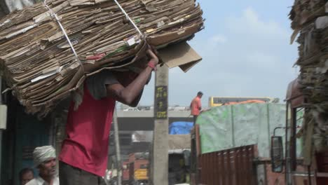 A-worker-carries-a-pile-of-cardboard-on-his-back-and-loads-it-onto-a-truck-along-with-many-other-piles