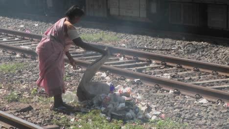 Una-Mujer-Arroja-Una-Bolsa-De-Basura-En-Las-Vías-Del-Tren