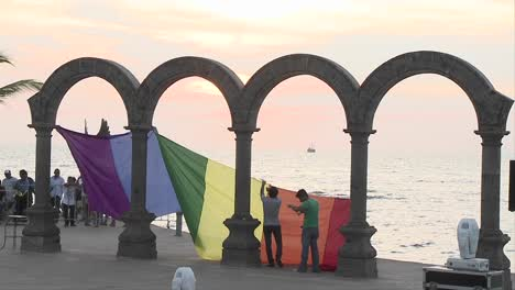 Gay-pride-flag-being-hung-from-the-arches-down-town-in-Puerto-Vallarta-beach-resort