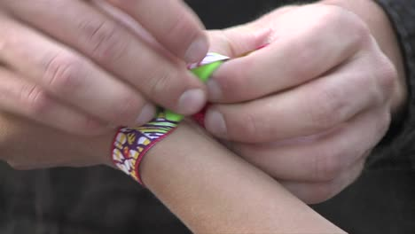 Friendship-bracelet-being-knotted-to-a-wrist