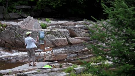 Un-Artista-Pinta-Un-Cuadro-Junto-A-Un-Río-En-La-Naturaleza