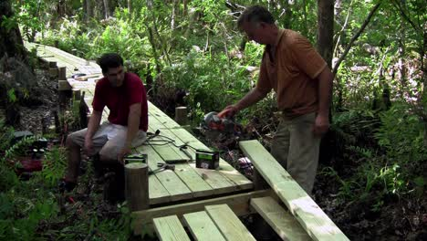 A-father-and-son-work-on-a-wooden-walkway-through-the-Everglades