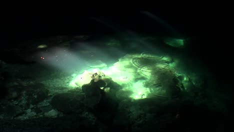 Green-pools-glimmer-in-the-sunlight-at-the-bottom-of-a-cave